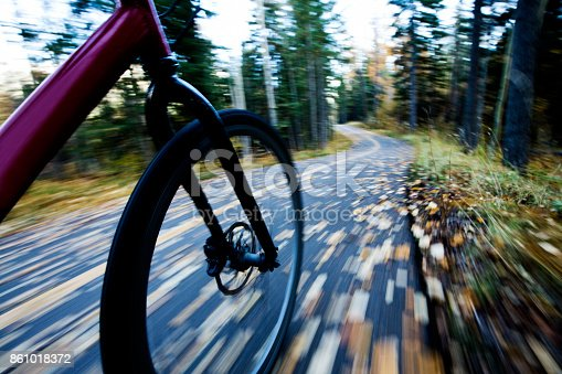 861018326 istock photo The view of the front wheel of a cyclo-cross commuter bike and the aspen leaves on a bicycle pathway in fall. 861018372
