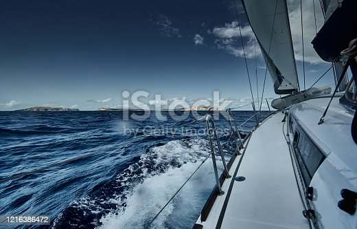 The view of the sea and mountains from the sailboat, edge of a board of the boat, slings and ropes, splashes from under the boat, sunny weather