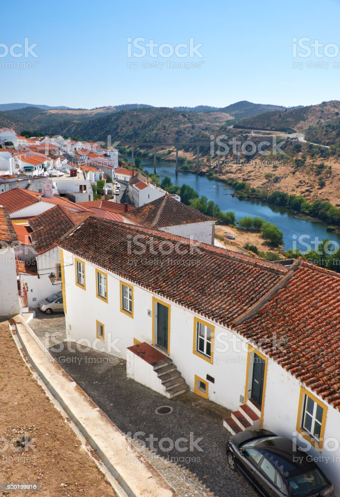 The view of tile roofs of Mertola with bridge across the valley of Guadiana river. Mertola. Portugal stock photo