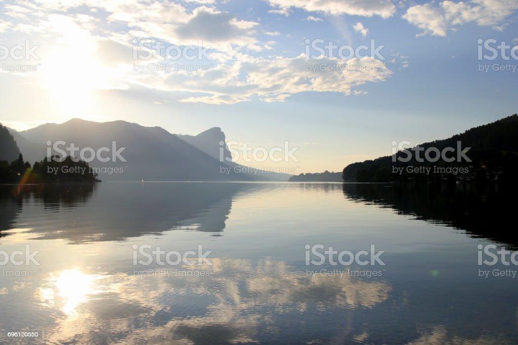 Der Blick auf den See mit den Bergen im Hintergrund in den sonnigen Tag. – Foto