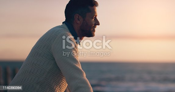 Shot of a handsome man watching the sun set at the beach