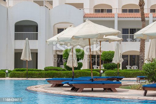 The view to the swimming pool, sun umbrellas and deck chairs in Sharm el Sheikh, Egypt. Travel and lifestyle concept