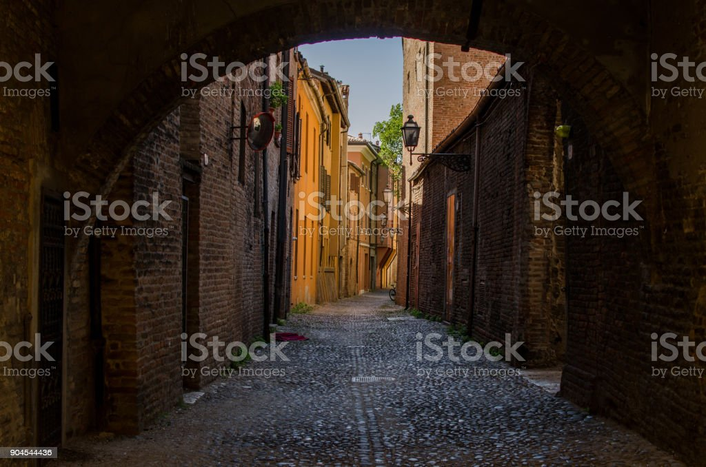 The view through the arches on picturesque medieval street of Ferrara stock photo