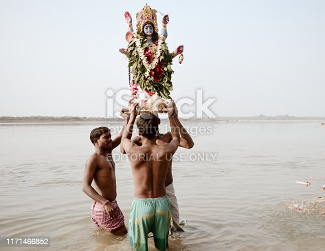 Bethuadahari, Nadia, West Bengal, India October 2018 - The Village People of Rural India lifting Goddess Idol before immersion in Ichhamati River. A typical natural scene depicting simple rural life. The river locally known as Bhagirathi, Churni or Jalangi.