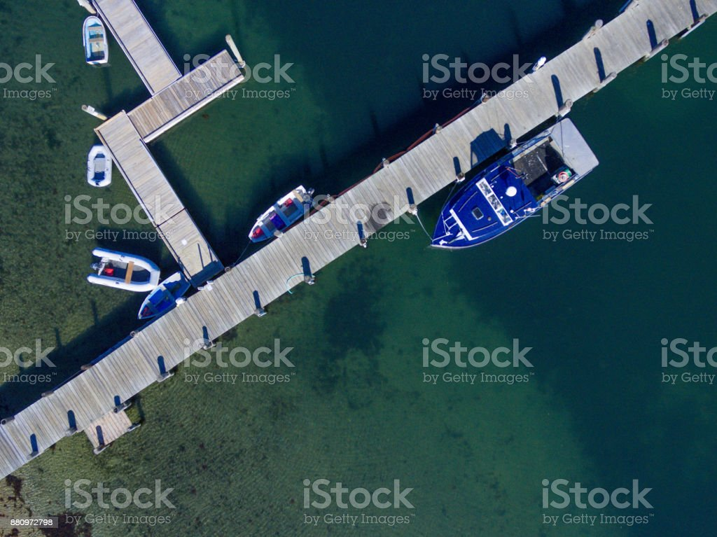 The Vineyard Haven Harbormaster boat tied to the dock as seen from an aerial view above stock photo