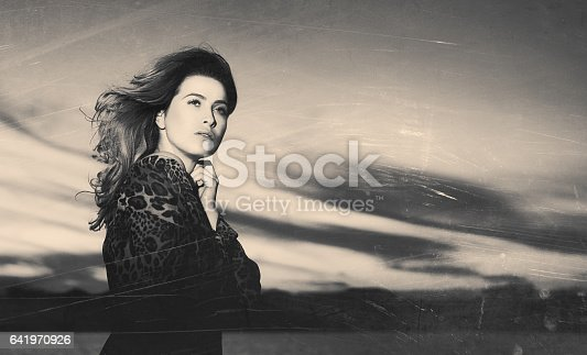 attractive woman posing in the sunset, thinking far away, photo taken through grass, vintage concept.