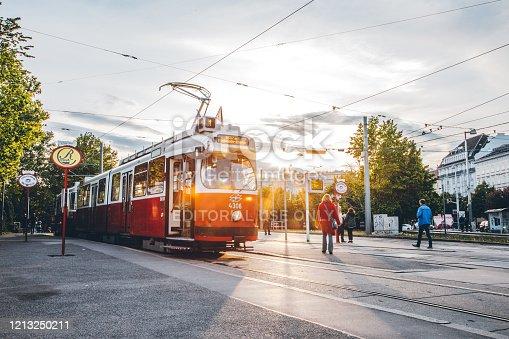 Typical red retro ring tram (Straßenbahn Haltestelle) at the station on a sunny day located in Karlsplatz, Vienna, Austria