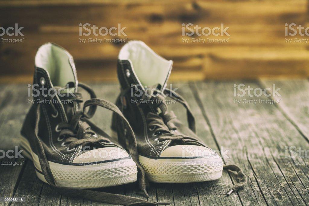 Os tênis vintage na velha mesa de madeira. - foto de acervo