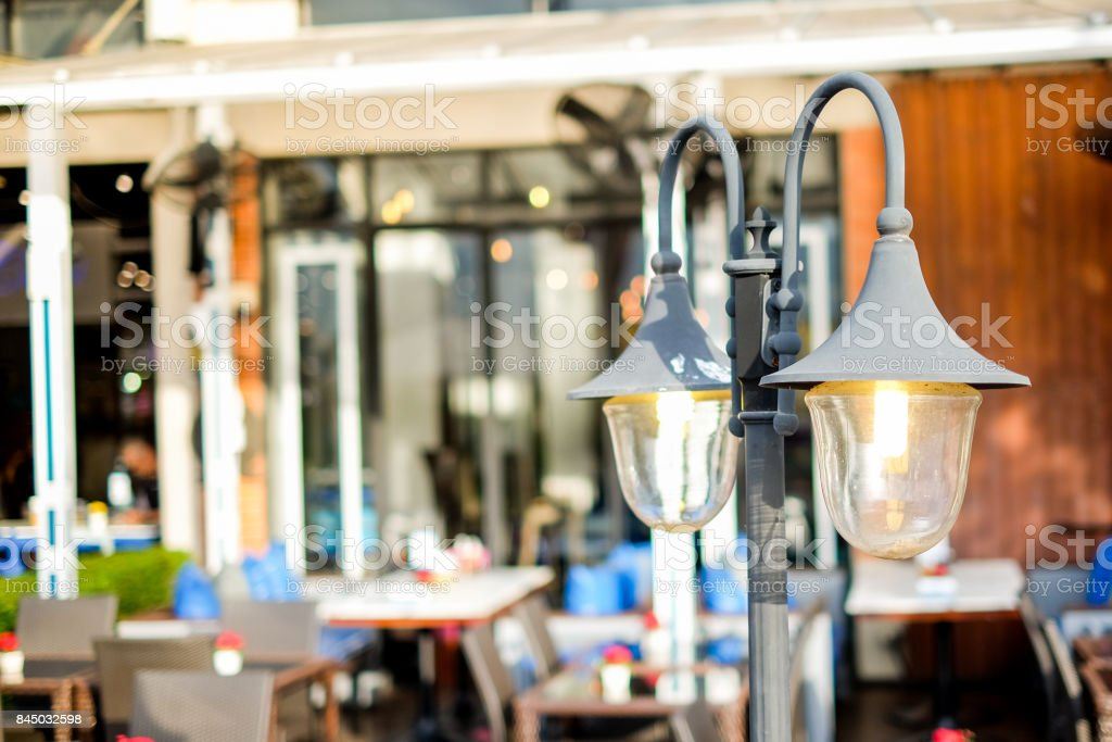 The vintage street lamp shine near the outdoor restaurant for...