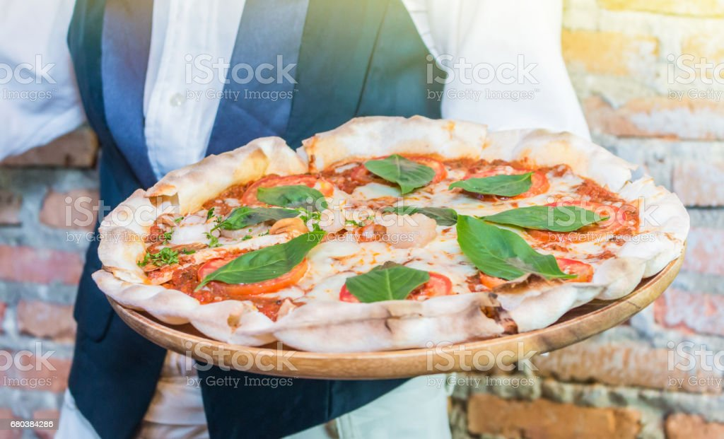 The waiter holding the tray hot pizza with melting cheese in the pizza shop ready for served to customer royalty-free stock photo