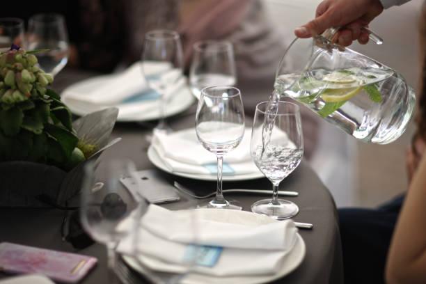 Der Kellner gießt Wasser mit Zitrone – Foto