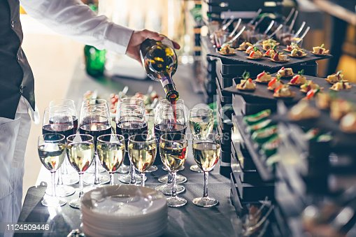 istock The waiter pours wine into glasses. Event catering concept. 1124509446