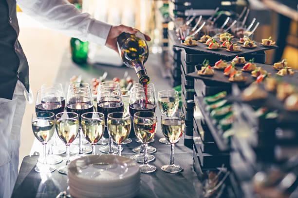 the waiter pours wine into glasses. event catering concept. - muita comida imagens e fotografias de stock