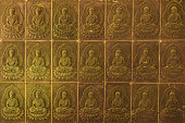 The wall in the temple is filled with buddhas. Religion Buddhism concept. Texture, background Buddhism.