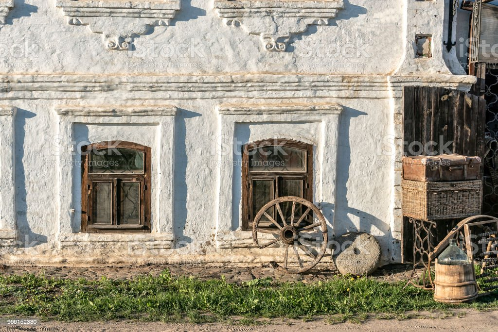 The wall of an ancient house near which there is an old wheel from a cart and a millstone from an ancient mill - Royalty-free Ancient Stock Photo