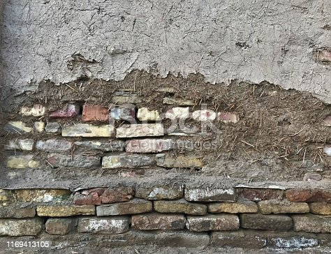 The wall of the old Adobe house in the ancient city, made of brick, covered with clay and straw