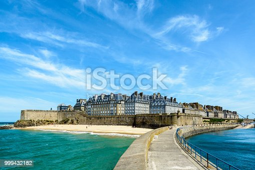 The walled city of Saint-Malo, France, with granite residential buildings protruding above the rampart and the Mole beach at the foot of the fortifications, seen from the breakwater.
