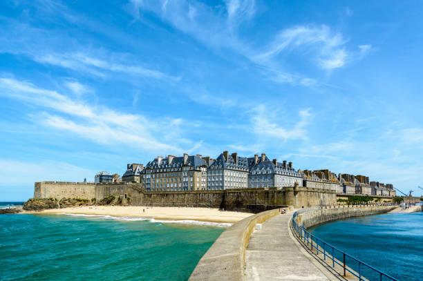 La ville fortifiée de Saint-Malo, en France, avec des bâtiments résidentiels de granit en saillie au-dessus du rempart et la plage du Mole au pied des fortifications, à partir de la digue. - Photo