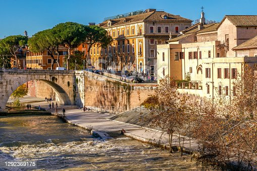 Rome, Italy, December 13 -- A warm autumnal light illuminates the Tiber riverbank, the Tiber Island and the Cestius Bridge, built in 46 BC at the behest of Lucius Sestius. The Tiber island its between the Roman Ghetto and Trastevere district. Image in High Definition format.