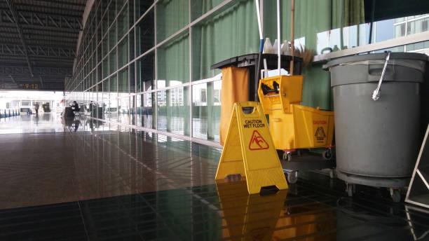 die warnschilder reinigen und warnen vor nassem boden. - hausmeister stock-fotos und bilder