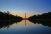 Sunrise at the Washington Monument in front of the Reflecting Pool in Washington DC, USA.