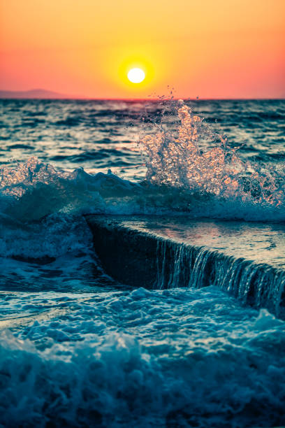 the wave hits a stone pier at sea, with sunset in the background - lepro stock pictures, royalty-free photos & images