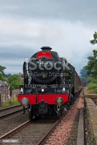 Lazonby, Cumbria, England - July 22, 2012: Preserved steam locomotive 46115, Scots Guardsman, heads the Waverley into Lazonby station on July 22, 2012, on the Settle to Carlisle railway.