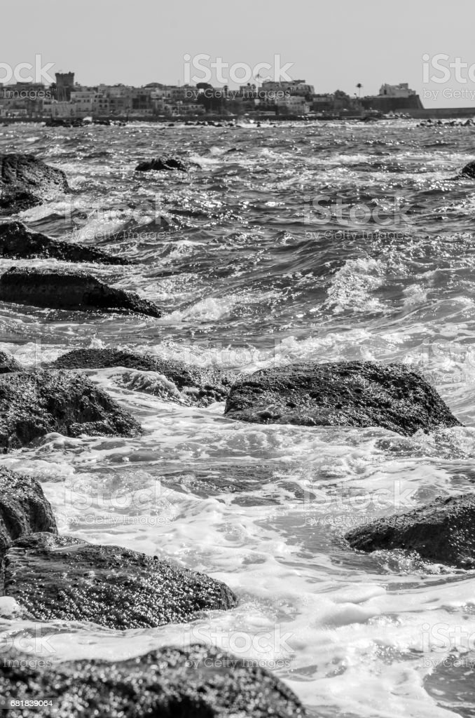 The waves crash on the cliff of Forio in Ischia stock photo