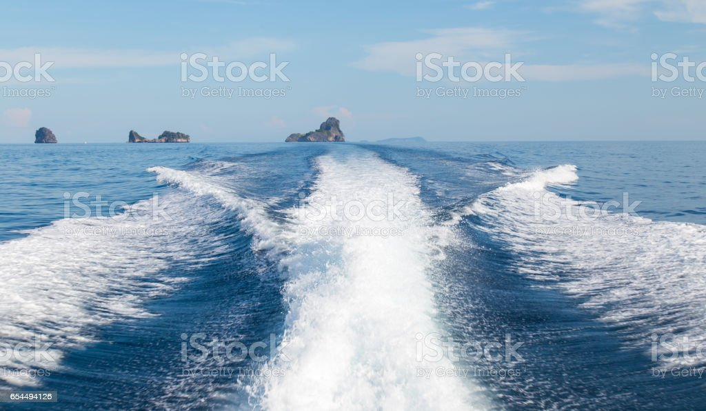 The waves from a high-speed boat and island background stock photo