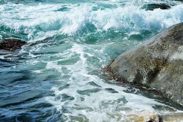 the waves vs. the volcanic rock in british virgin islands on a sunny day - deign stock pictures, royalty-free photos & images