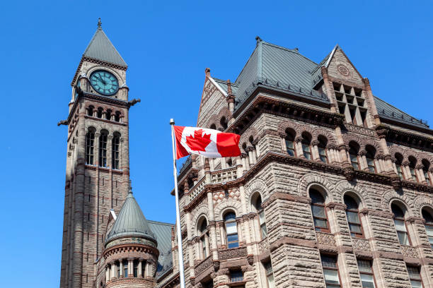 The waving Canadian flag with Old City Hall in background in Toronto, Canada. stock photo