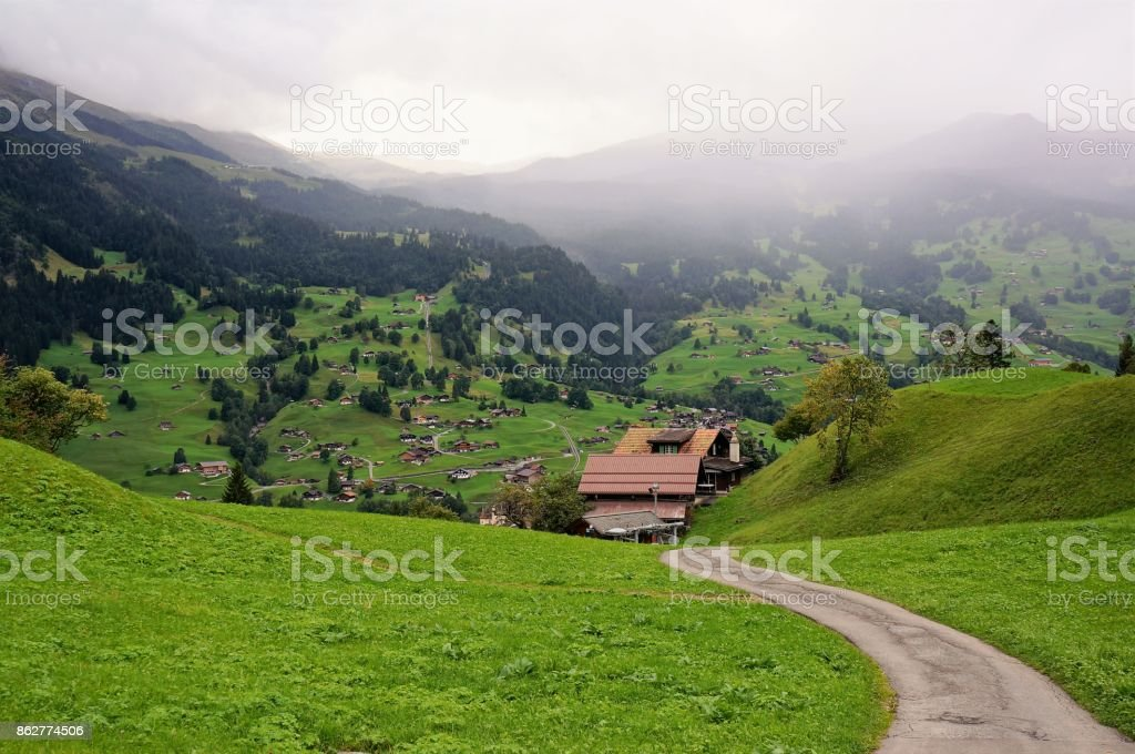 The way down to village and little house and the green field in Grindelwald stock photo