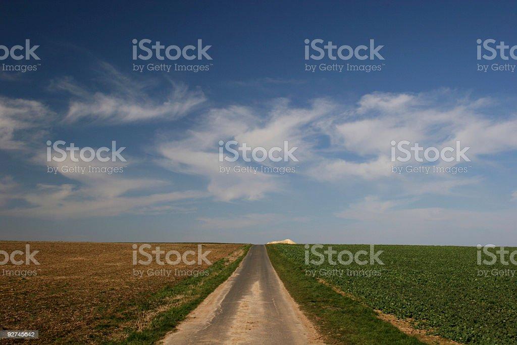 Die gerade Feldweg vor Wolken Lizenzfreies stock-foto
