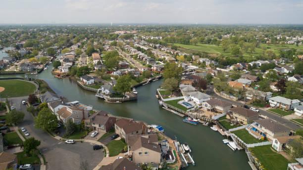 Das wohlhabende Wohnviertel in Oceanside, Queens, New York City, mit Häusern mit Pools auf Hinterhöfen und Piers mit Booten entlang der Kanäle. – Foto