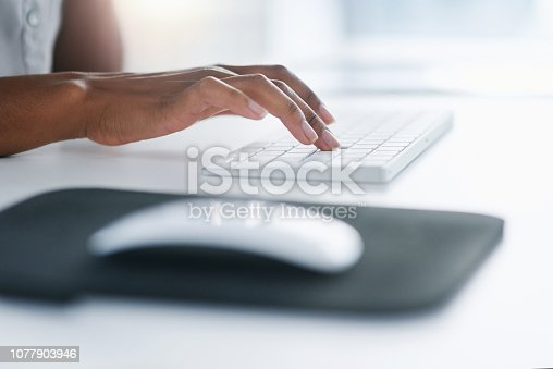 Closeup shot of an unrecognizable woman typing on a keyboard in an office