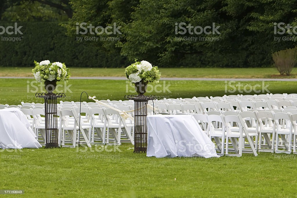 Chairs and flower arrangements await guest to a wedding ceremony