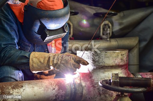 The welder is assembling valve to the pipe line with Tungsten Inert Gas Welding process (TIG). The welder wears protective equipment with a welding mask and heat resistant gloves.