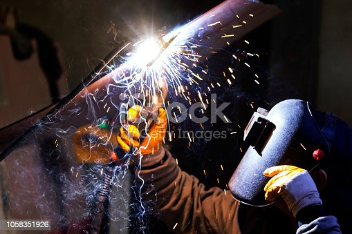 The welder is welding to a steel plate. Welding is the process of joining two plastic or metal parts by melting them with or without using a further molten material.