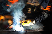 The welder is welding with shielded metal arc welding, manual metal arc welding or stick welding. Electric current is used to strike an arc between the base material and consumable electrode rod.