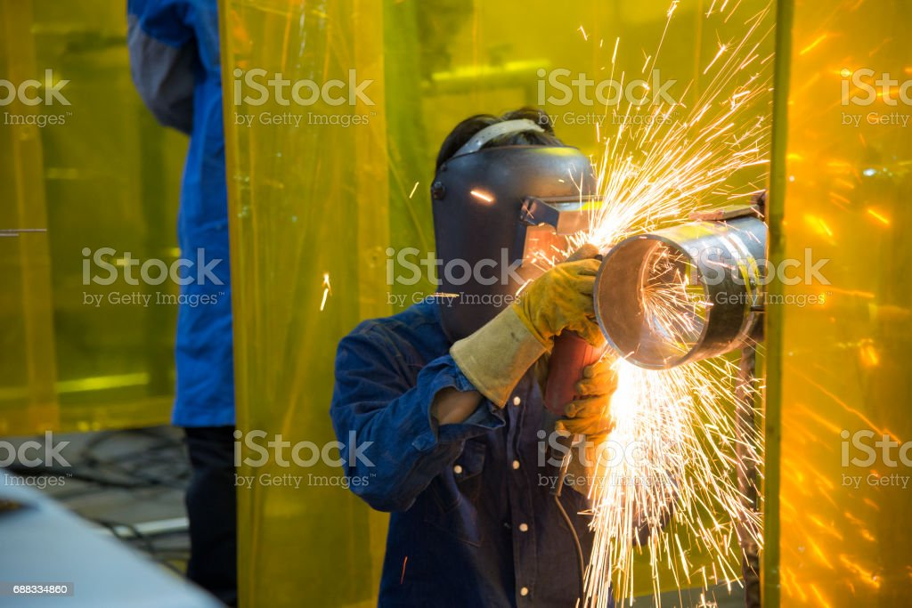 The welding craftsman grinding the steel tube stock photo