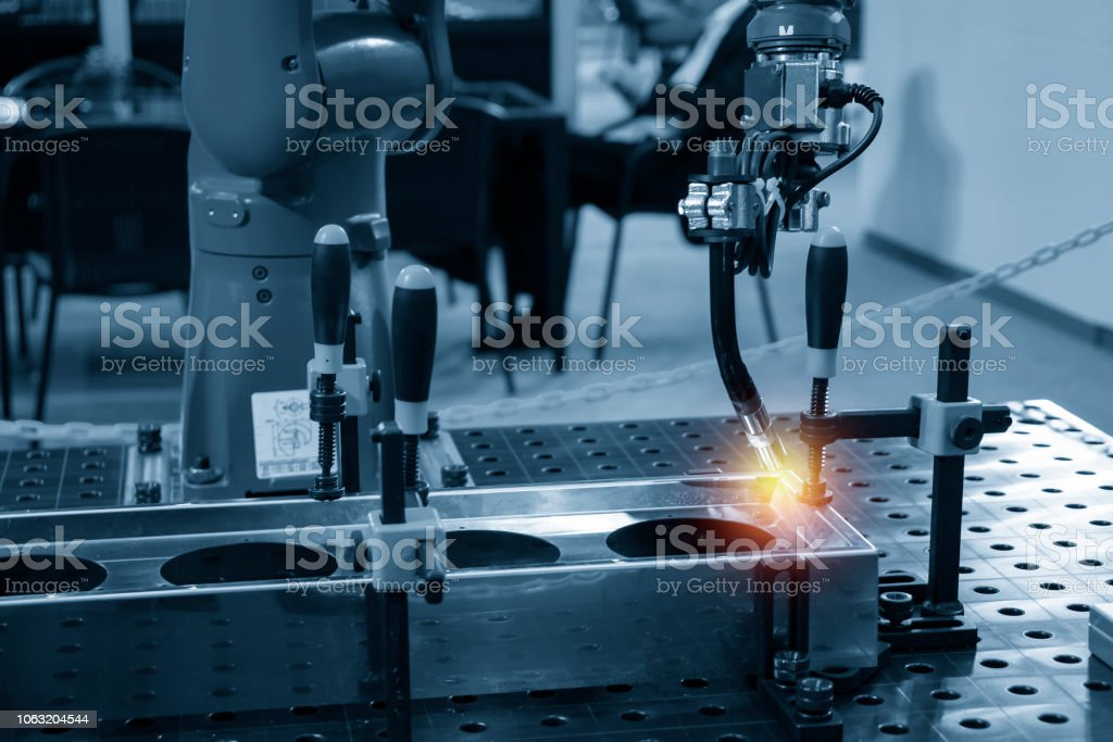 The welding robot machine for welding automotive part in the light blue scene. The welding robot machine for welding automotive part in the light blue scene.Industrial 4.0 concept for modern manufacturing process. Accuracy Stock Photo