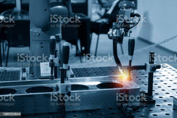 The Welding Robot Machine For Welding Automotive Part In The Light Blue Scene Stock Photo - Download Image Now