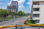 Bogota, Colombia - March 28, 2020: The normally extemely busy section of the Westbound carriageway of Calle 100 or 100 Street, in the Colombian Capital city of Bogota is almost deserted due to the Coronavirus Lockdown in the Country. A few public transport blue busses can be seen in the distance. In the middle of the image, the bicycle lanes can be seen; there is no one cycling today. In the forground is the ramp to the Pedestrian footbridge. The altitude at street level is about 8500 feet above mean sea level. Image shot in the bright noonday sunlight. Horizontal Format.