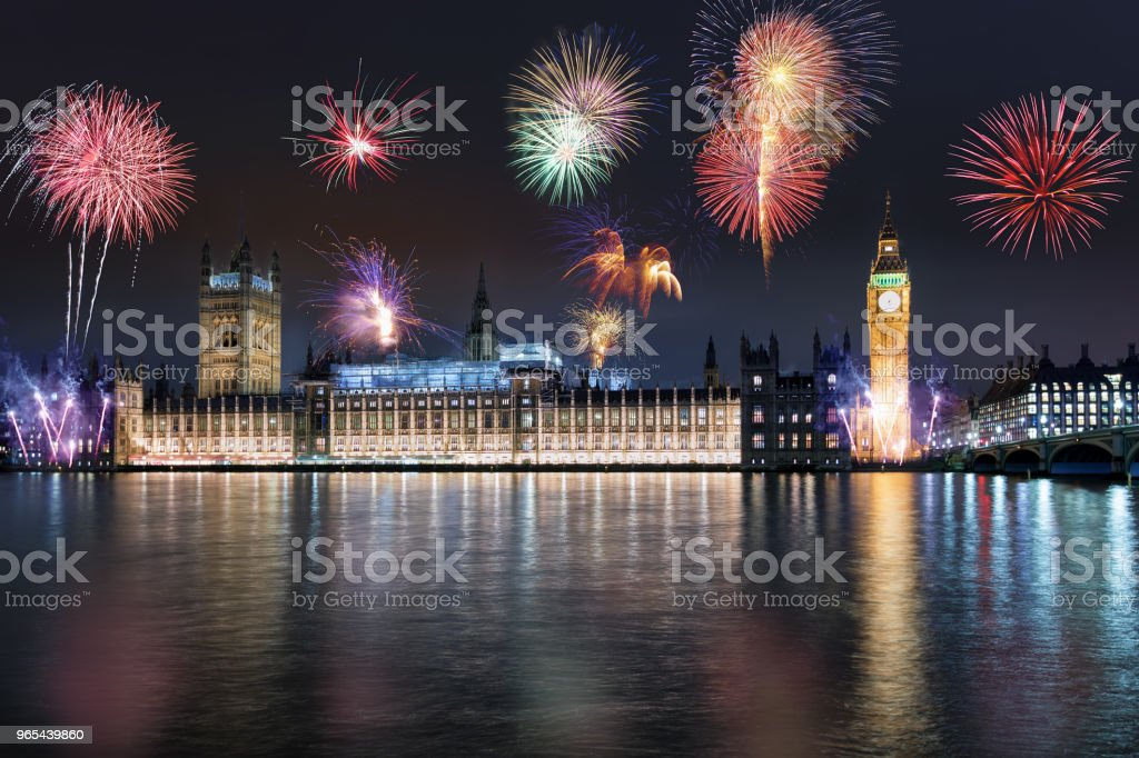 The Westminster Palace and Big ben tower during night with fireworks royalty-free stock photo