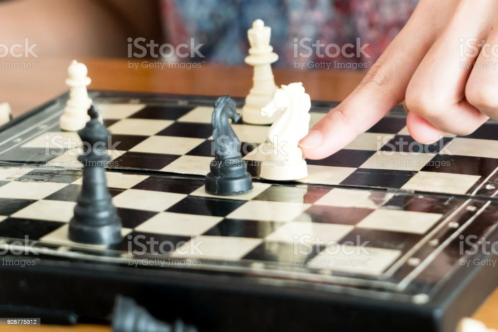 the white chess on women hand is flighting with black, think, discuss, committed, competition, winner, successful, dedicate concept stock photo