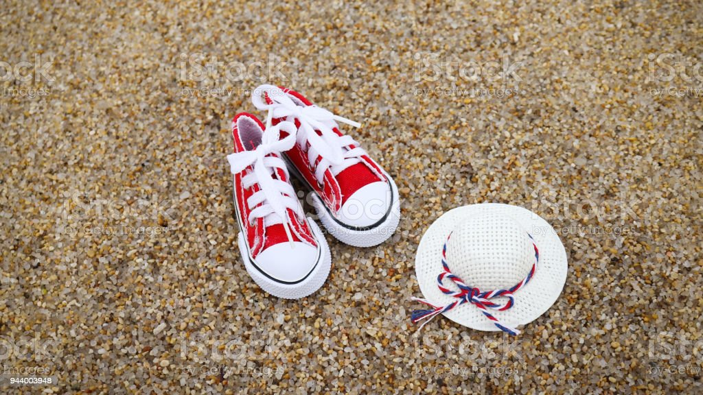 The white hat and red sneakers on the sand. stock photo