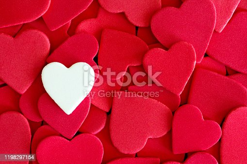 A single white heart on a background of red hearts with copyspace. Love / Heart health concept image.