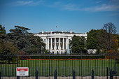 The White House, next to fence on 1600 Pennsylvania Ave.  Home of the President of the United States of America in Washington, DC USA. Blue sky background.