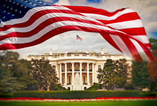 the white house with waving american flag - white house стоковые фото и изображения