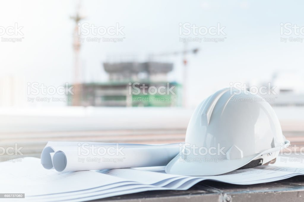 The white safety helmet and the blueprint at construction site with crane background stock photo